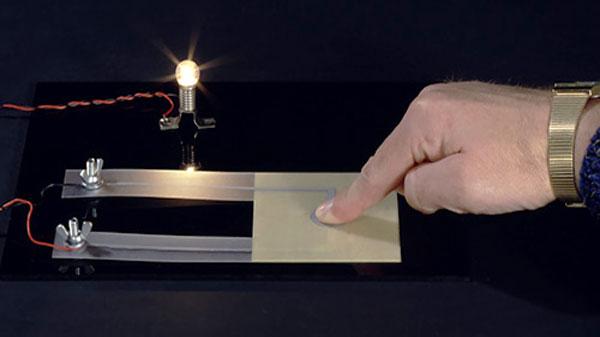 Finger tippt auf Folie und bringt Glühbirne zum leuchten